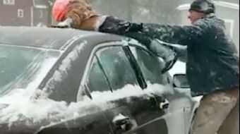 Bir baba, arabasının üzerindeki karları temizlemek için çocuğunu kullandı